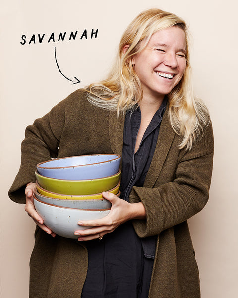 A woman in an olive coat laughs while holding a stack of mixing bowls.