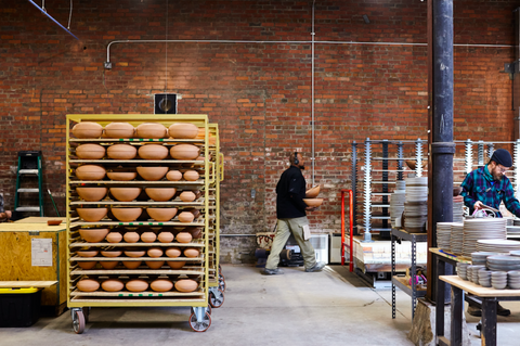 East Fork's ceramic factory with stacks of pottery waiting to be fired and glazes, with East Fork team members at work.