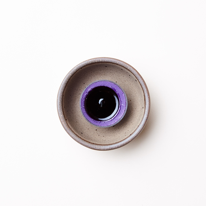 A Bitty Bowl by East Fork Pottery in Morel glaze with a half-burned purple votive candle place in the center
