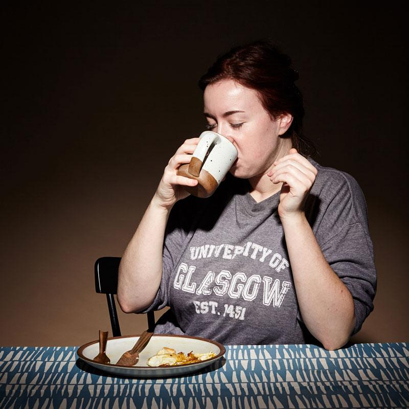 A woman sits alone at a table drinking out of an East Fork Mug and eating eggs off of an East Fork Dinner Plate in Eggshell