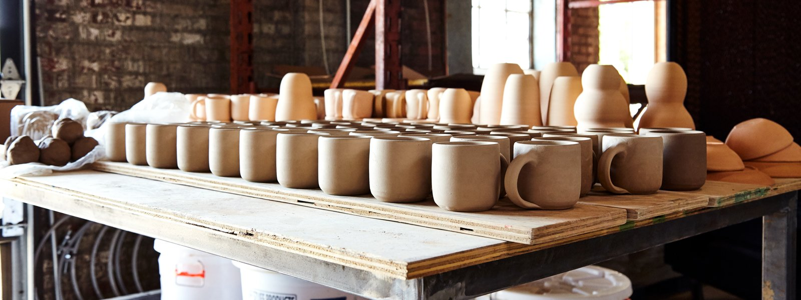 Stacks of Third Wave Mugs by East Fork Pottery and Counter Culture Coffee waiting to be glazed