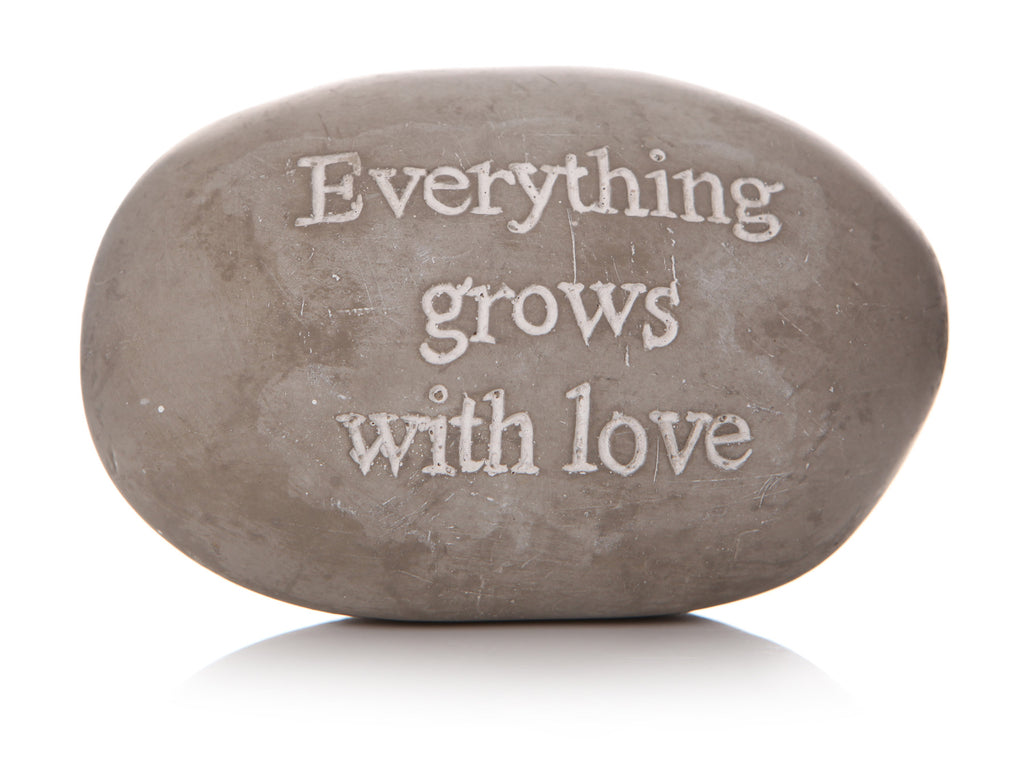 Grey pebble with 'Everything grows with love' writing in white