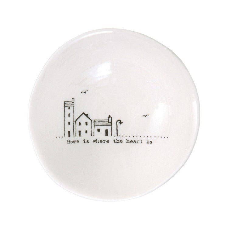 Home is where the heart is written on a white bowl with house illustration