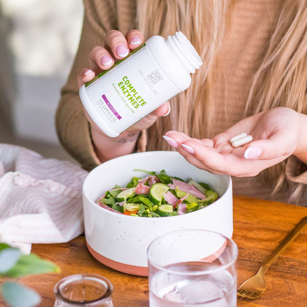 Woman Taking Two Complete Enzymes Tablets Before Eating a Bowl of Salad - Amy Myers MD®