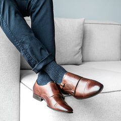 A man in casual clothes sitting down and wearing cobb brown leather Monk strap shoes