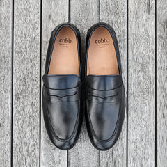 A pair of Cobb black leather loafers on a wooden floor