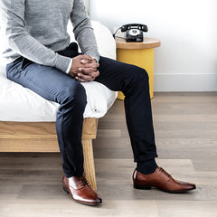 a man in casual clothes and wearing cobb brown leather derby shoes sitting on the corner of a bed