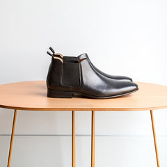 A pair of Cobb black leather chelsea boots on top of a table