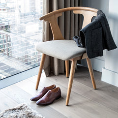 A pair of Cobb brown leather brogues on the floor next to a chair and a jacket
