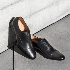 A pair of Cobb Black Leather Oxford Shoes Leaning Against a Wall