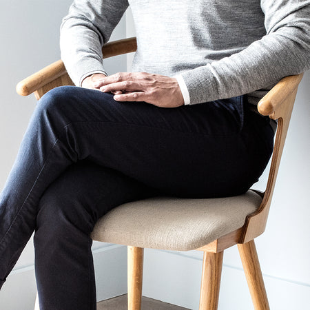 a gentleman relaxing in a chair wearing smart casual clothes