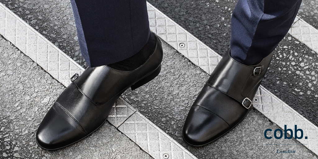 a man wearing men's black double monk strap shoes with a navy suit