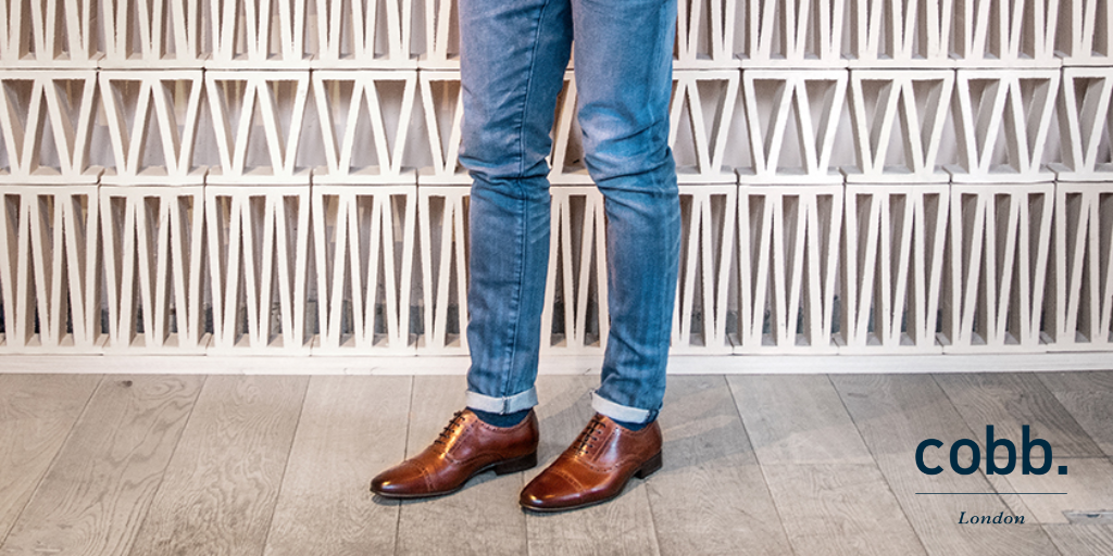 a man wearing a pair of men's brown leather brogue shoes and denim jeans