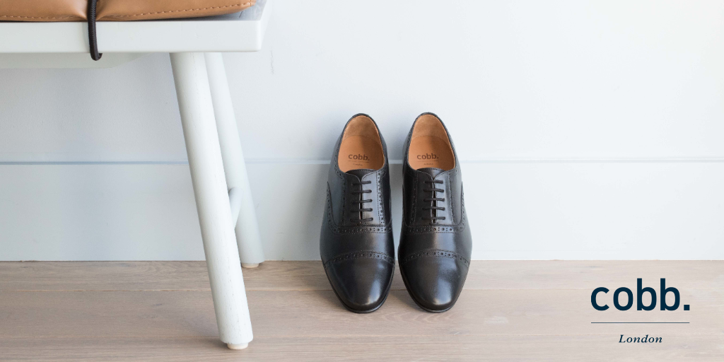 a pair of men's black leather brogue shoes leaning against a wall