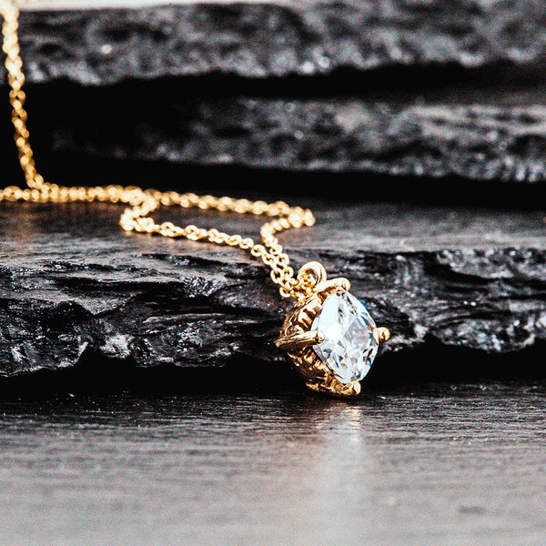 a bezel set diamond in a gold necklace
