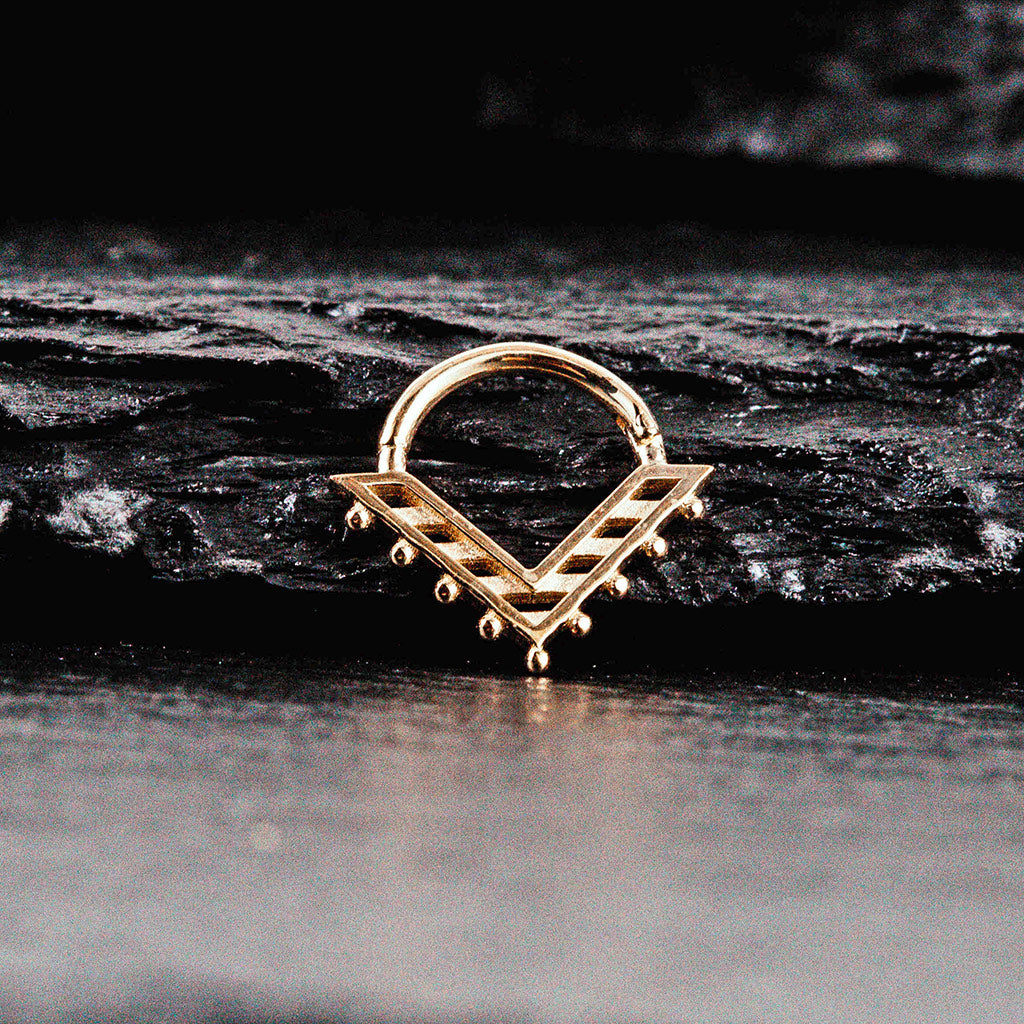 a Triangular nose ring. In yellow gold.