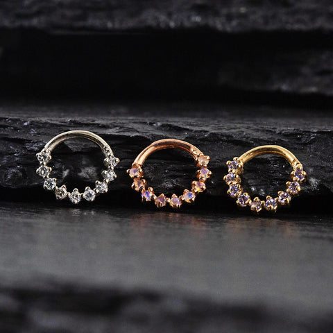Three gold nose rings side by side
