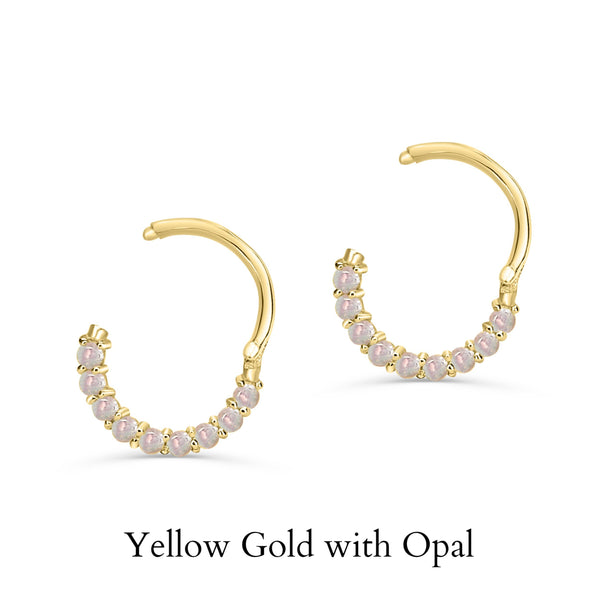 a yellow gold septum clicker with opal