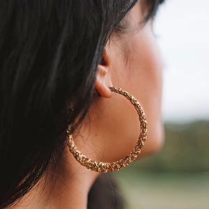 A women with dark brown hair wearing gold hoop earrings.