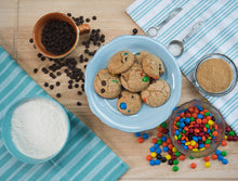 Ani & Fabi presents M&M S'mores All-In-One cookies, pre-measured ingredients including Granulated Sugar, Brown Sugar, Vanilla Extract, Flour, Graham Crumbs, Baking Powder, Baking Soda, Sea Salt, M&M's, Semi-Sweet Chocolate Chips, Mini Marshmallows. Convenient, no-waste, hassle-free baking experience delivered from Windsor, Ontario.