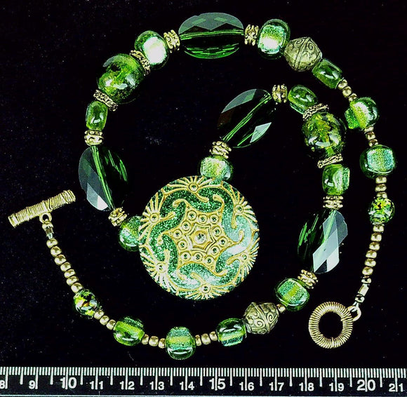 Green glass 22 inch necklace with centered pendant and brass toggle clasp