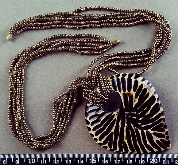 Brown/metallic multi strand 18 in glass necklace with 3.5 inch carved wood pendant, barrel clasp