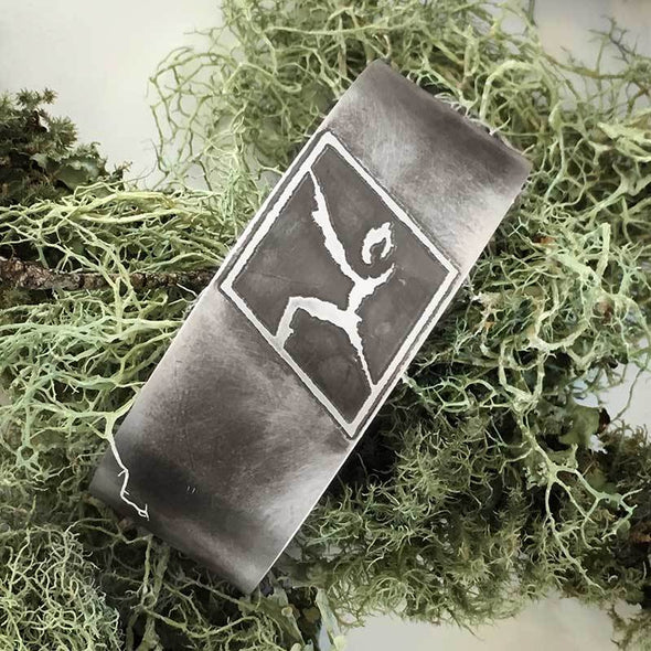 Wide oxidized silver rock climbing cuff on grass