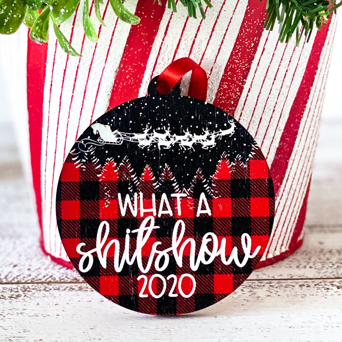 What a shitshow on round ornament. Red and black buffalo plaid background with Santa's sleigh