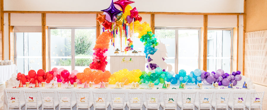 unicorn party set up with a themed children's table and balloons