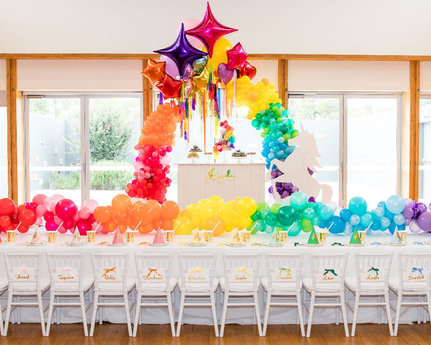 Unicorn Party setup with Kids Table and Rainbow balloon party decorations