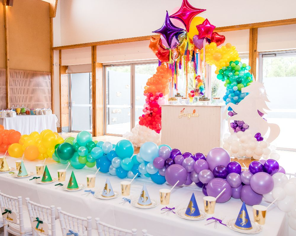 Kids table with rainbow balloon runner with life size unicorn
