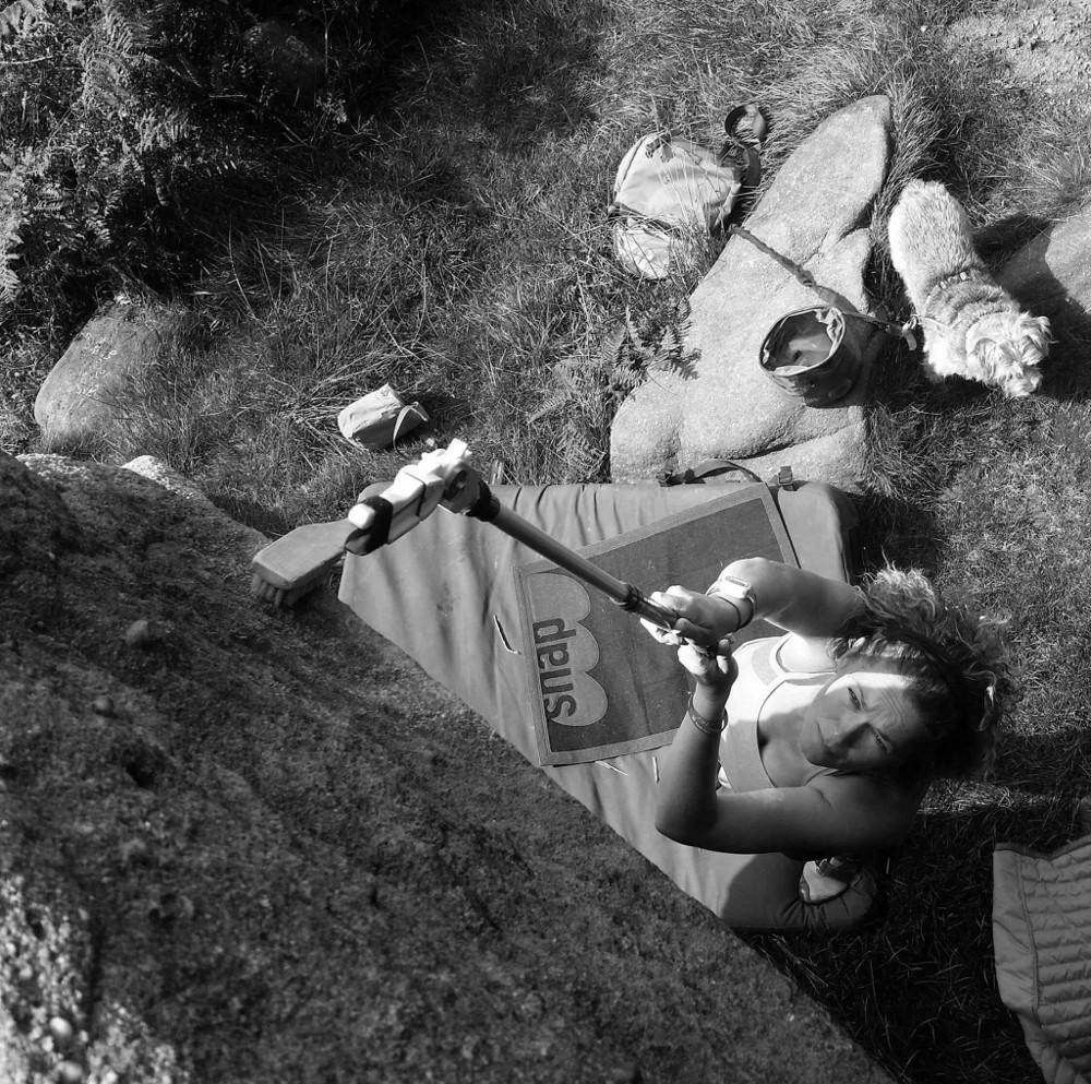 Beta Project bouldering Brush Stick shown in black and white photo in use on real rock boulder