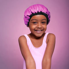 Young girl wearing a pink Lava Cap heat cap for deep conditioning hair treatments