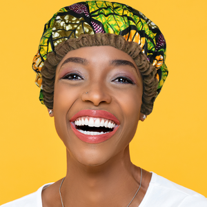 Woman wearing Ankara mixed-green leaf print microwavable flaxseed-filled deep conditioning heat cap with a huge smile