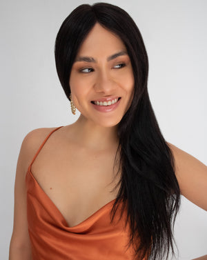 Happy woman wearing a long straight wig with middle parting and an orange dress
