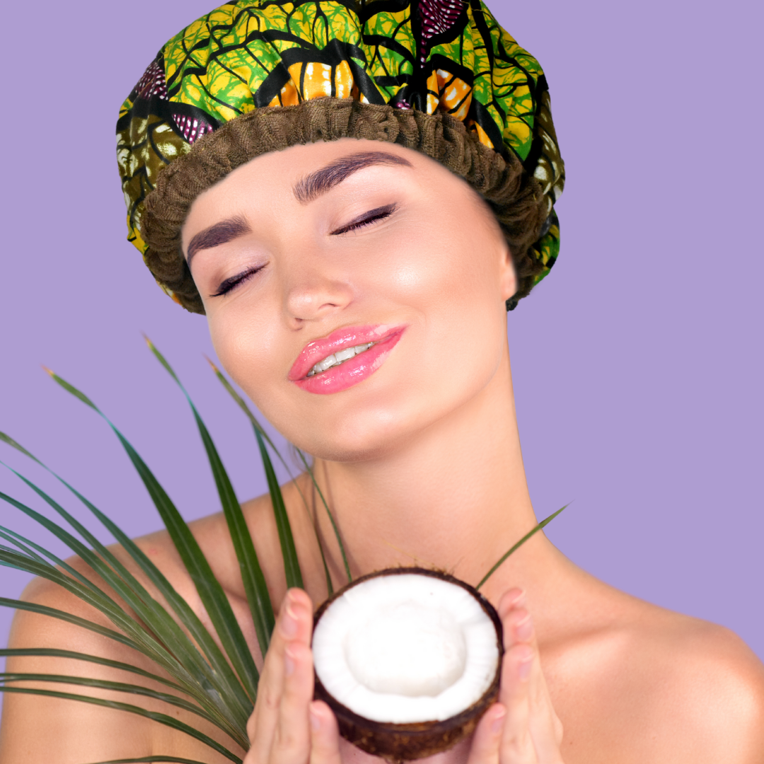 Woman wearing Ankara mixed-green leaf print microwavable flaxseed-filled deep conditioning heat cap, holding a coconut and smiling