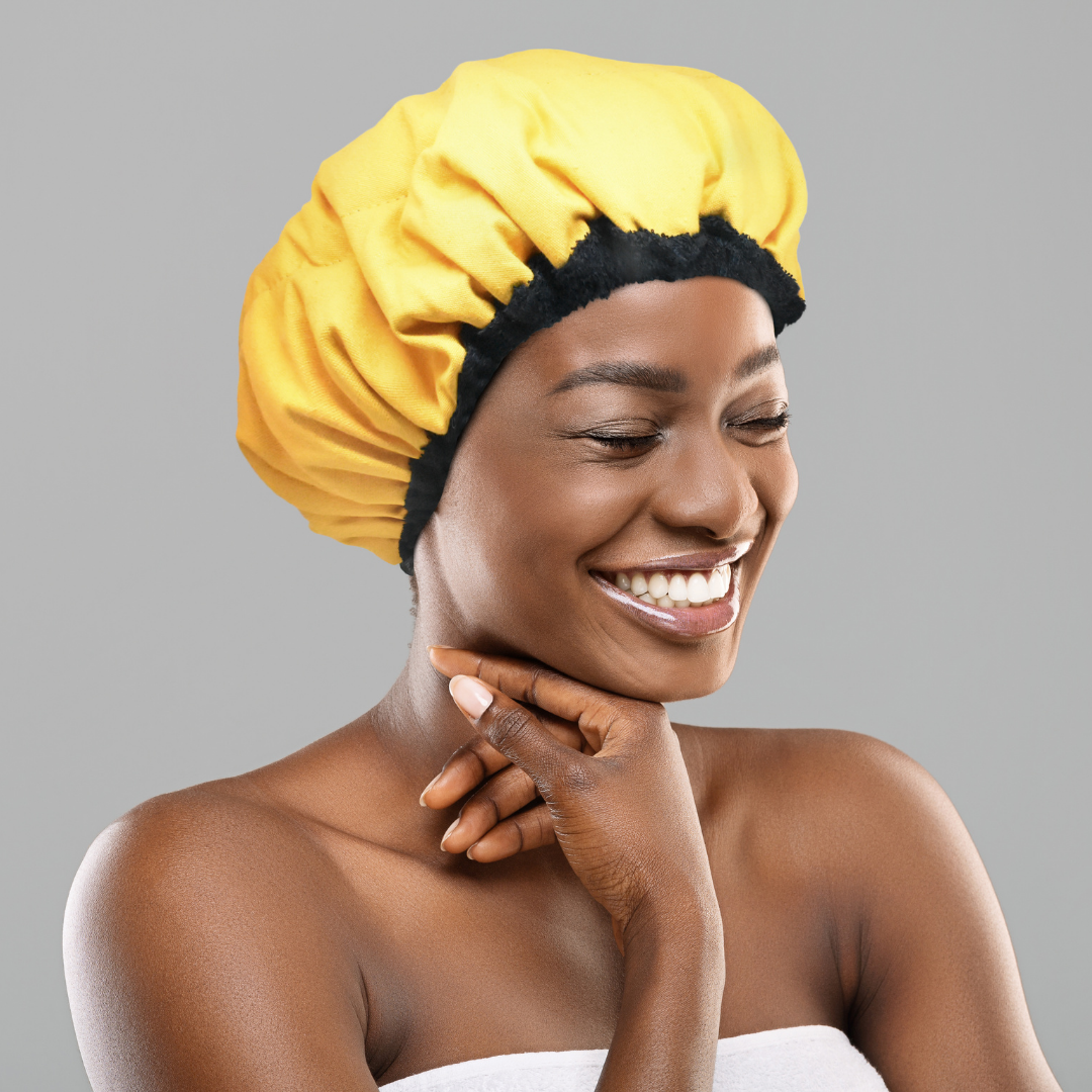 Woman wearing amber yellow microwavable flaxseed-filled deep conditioning heat cap, standing at an angle while smiling with her eyes closed