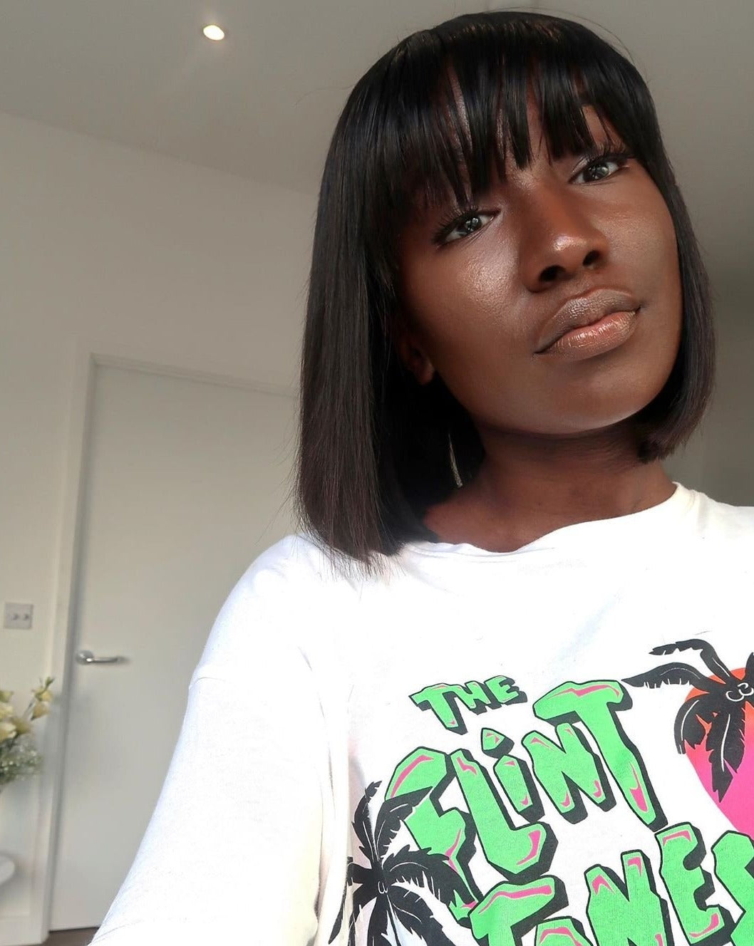 woman wearing full lace frontal bob wig with fringe and flintstones tshirt