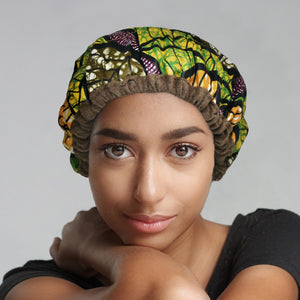 Woman wearing an Ankara print in a mixed-leaf pattern microwavable flaxseed-filled deep conditioning heat cap and black t-shirt while looking into camera with piercing eyes