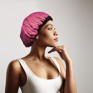 Woman wearing pink microwavable flaxseed-filled deep conditioning heat cap