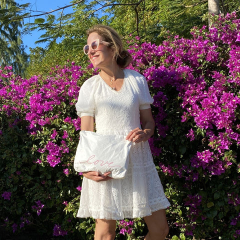 woman in a white dress holding a travel pouch in front of magenta flowers