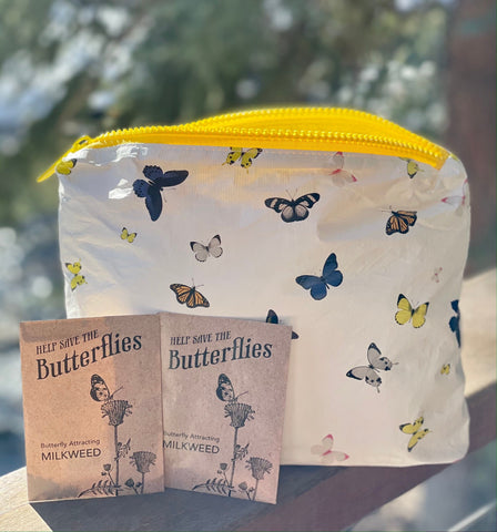 white travel pack with a colorful butterfly pattern and milkweed seed packets
