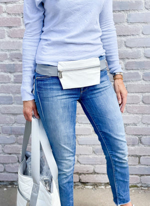 woman in blue jeans wearing shimmer white fanny pack