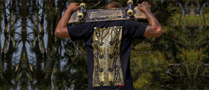 Skateboarder holding skateboard above shoulders wearing gold maori tamoko design on black tshirt