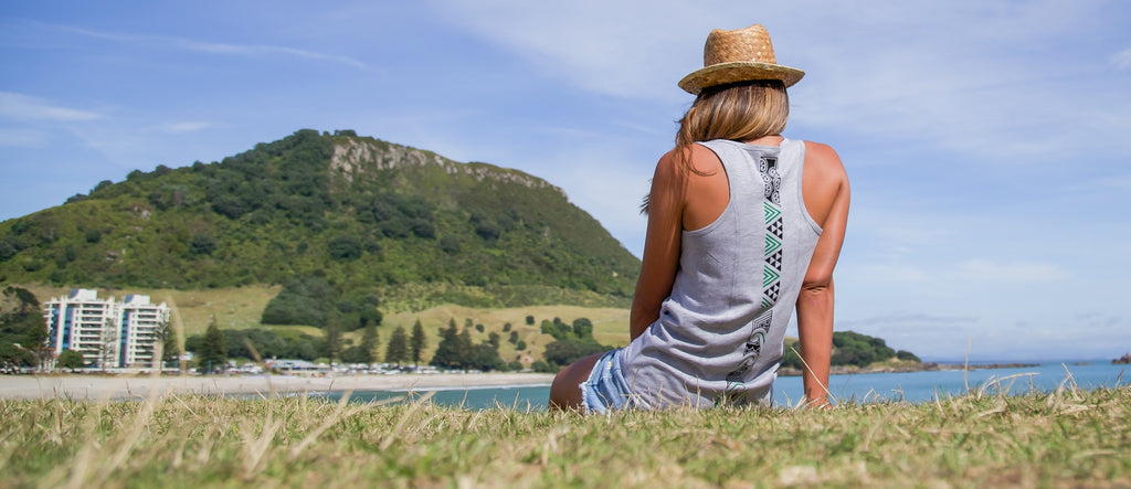 Beautiful model wearing a women's grey singlet with maori design overlooking Mount Maunganui