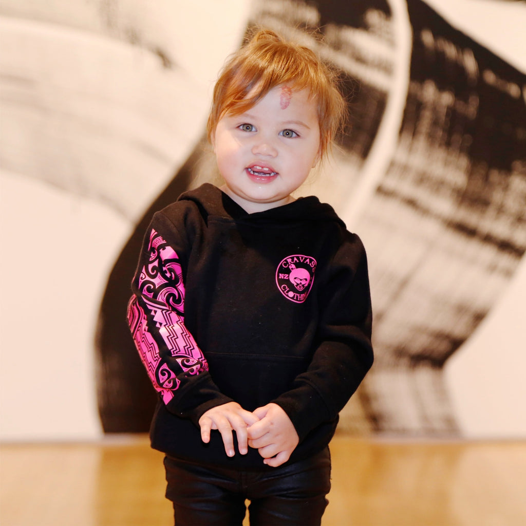Cute toddler model wearing a black hoodie with fluro pink maori designs on the sleeve.