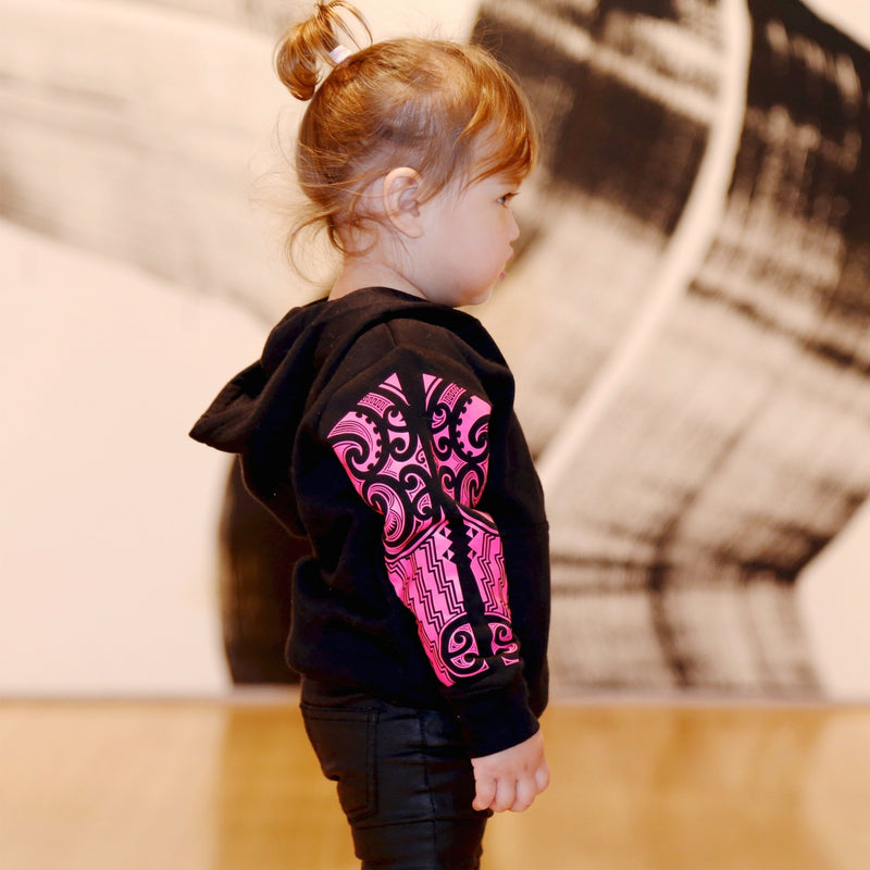 Cute toddler model wearing a black hoodie with fluro pink maori designs on the sleeve. Side view.
