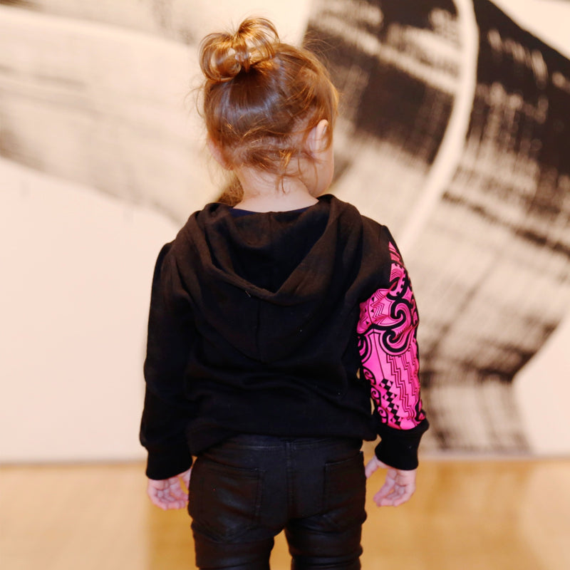 Cute toddler model wearing a black hoodie with fluro pink maori designs on the sleeve. Back view.