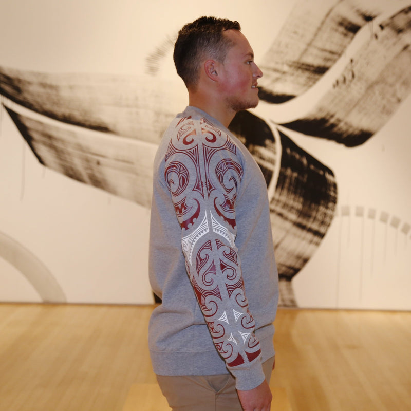 Maroon and white ta moko sleeve design on grey box crew jersey.