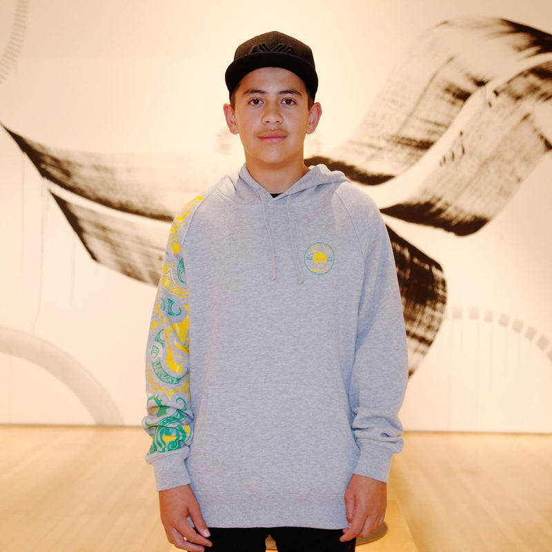 Kids grey hoodie from cravass clothing with yellow and green NZ maori ta moko sleeve.